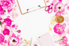 Stylish pink workspace with clipboard, notebook, rose flowers and accessories on white background. Flat lay, top view. Stock Images