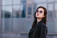 Stylish portrait of beautiful brunette girl in glasses, which poses against a background of dark city background Royalty Free Stock Image