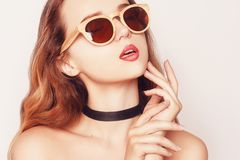 Stylish portrait of a beauty model girl wearing dark wooden sunglasses. Closeup fashion beautiful woman with long curly hair Royalty Free Stock Photos