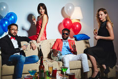 Stylish portrait of elegant friends. Stylish Afro-American men in sunglasses sitting in living room and holding disco ball in hand, two pretty women and Asian Royalty Free Stock Photography