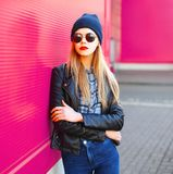 Stylish portrait young blonde woman in rock black style jacket, hat posing on city street over colorful pink wall stock photography