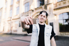 Stylish and positive student in cap and denim jacket makes selfie mobile phone. On the campus of the university. Student life. Focus on your phone Royalty Free Stock Photography