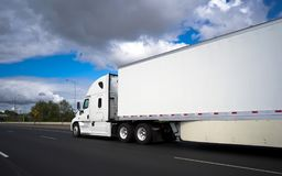 Long haul big rig semi truck transporting commercial cargo in dr. Stylish powerful long haul big rig white semi truck with high comfort cabin transporting royalty free stock photography