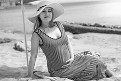 Stylish pregnant woman in long dress relaxing on beach Stock Photos