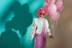 Stylish pretty girl in bright wig holding pink balloons. And looking away stock photos