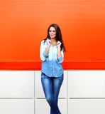 Stylish pretty smiling woman posing against colorful wall stock photography