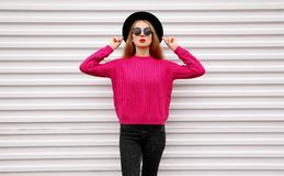 Stylish pretty woman model posing in colorful pink knitted sweater, black round hat on white wall. Background royalty free stock image