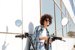 Stylish pretty woman in sunglasses using mobile phone. While standing against the wall outdoors with a motorbike Royalty Free Stock Images