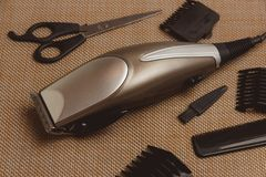 Stylish Professional Hair Clippers, accessories on brown background Royalty Free Stock Images