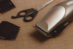 Stylish Professional Hair Clippers, accessories on brown background Royalty Free Stock Photos