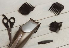 Stylish Professional Hair Clippers, accessories on wood background Royalty Free Stock Image