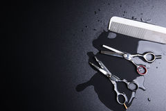 Stylish Professional Barber Scissors and white comb on black bac Stock Photography