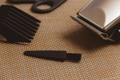 Stylish Professional Hair Clippers, accessories on brown background Royalty Free Stock Photography