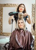 Stylish professional, hairdresser doing hairdoing to the client with a hair dryer on the background of the hairdresser`s stock photos