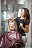 Stylish professional, hairdresser doing hairdoing to the client with a hair dryer on the background of the hairdresser`s stock photo