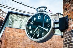Stylish public analog clock hanging on brick wall showing time in Brooklyn, New York during daytime. Stylish public analog clock hanging on brick wall showing royalty free stock images