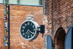 Stylish public analog clock hanging on brick wall showing time in Brooklyn, New York during daytime. Stylish public analog clock hanging on brick wall showing royalty free stock photo
