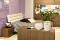 Stylish purple and white bed in modern bedroom Stock Photography