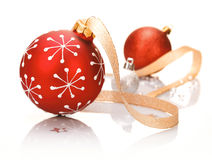 Stylish red Christmas background. With a bauble patterned with snowflakes and a decorative ribbon on a reflective white studio surface Stock Photos