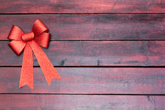 Stylish red Christmas bow and ribbon. In the top corner on mahogany stained wooden boards with copy space for your seasonal holiday greeting Royalty Free Stock Photography