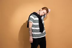 Stylish red-haired guy in a striped shirt with tattoo on his hand is posing with black sweater on his shoulders on the stock photography