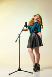 Stylish red-haired woman in leather skirt with suspenders holdin. Beautiful young singer with eyes closed holding mic.Studio shot Stock Images