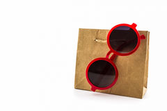 Stylish red sunglasses hanging on brown shopping bag. Stock Image