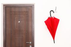 Stylish red umbrella hanging near door. On wall stock photo