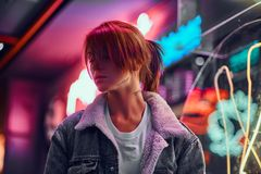 Stylish redhead girl standing in the night on the street. Illuminated signboards, neon, lights. royalty free stock photography