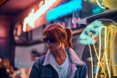 Stylish redhead girl standing in the night on the street. royalty free stock photography