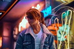Stylish redhead girl standing in the night on the street. royalty free stock photos