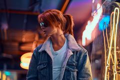 Stylish redhead girl standing in the night on the street. royalty free stock photo