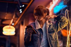 Stylish redhead girl using a phone while leaning on the illuminated signboard in the night on the street. royalty free stock photos