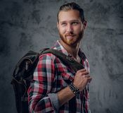 Redhead urban traveller male holds backpack. Stylish redhead urban traveller male holds backpack on grey background in a studio Stock Images