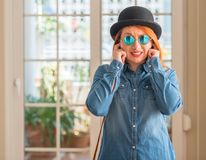 Young beautiful redhead woman at home. Stylish redhead woman wearing bowler hat and sunglasses covering ears with fingers with annoyed expression for the noise stock photography