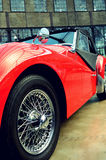 Stylish retro red car with a wheel with spokes and metallic mirr. Or in vintage style Stock Photography