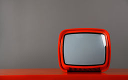 Stylish retro TV. Red retro TV on a red table Stock Images