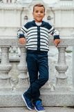 Stylish little boy in sunglasses and fashionable clothes . Children`s fashion. Stylish rich little boy in fashionable clothes . Leaned on Granite-stone handrails Stock Image