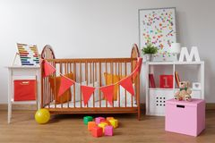 Stylish room for babygirl. Photo of stylish room for babygirl with wooden crib Stock Photo