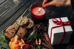 Stylish rustic christmas wallpaper with hand lighting up candle. And presents with red ribbon and cookies fruits on wooden background with green branches Stock Photography
