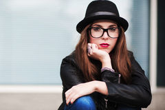 The stylish sad city girl in sunglasses leans a cheek on a hand Royalty Free Stock Photo