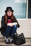 The stylish sad urban girl in sunglasses sits on steps Stock Photo