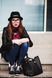 The stylish sad urban girl in sunglasses sits on steps.  Stock Photo