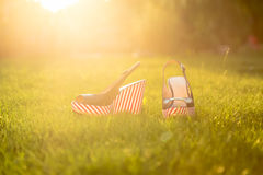 Stylish sandals, lie on the grass. In the garden Stock Photos