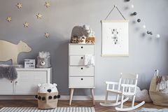 Stylish scandinavian nursery interior with hanging mock up poster, natural toys, teddy bears, children`s accessories and design royalty free stock image