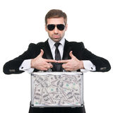 Stylish security guard presenting a metal suitcase full of U.S. Royalty Free Stock Photo