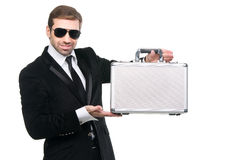 Stylish security guard presenting a metal suitcase. Stock Photo