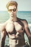 Stylish seducer man at sea. Fashion sunglasses and hair style. A handsome boy with sunglasses. Intense lights. Sunshine. In the background the Mediterranean stock image
