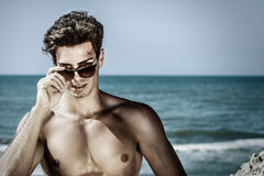 Stylish seducer man at sea. Fashion sunglasses and hair style. A handsome boy with sunglasses looking intensely discovering eyes. In the background the Royalty Free Stock Image
