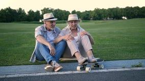 Stylish senior couple sitting with a skateboard stock video
